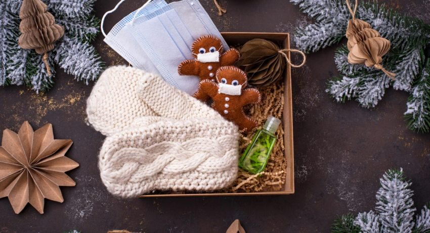 Christmas care package with mask, antiseptic, knitted mittens and Gingerbread man from felt